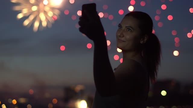 Una-chica-utiliza-un-sartphone-durante-un-fuego-artificial-4K