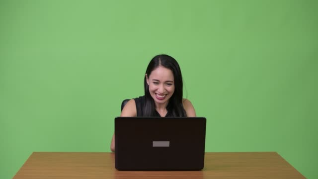 Young-Asian-businesswoman-using-laptop-with-young-man-getting-angry