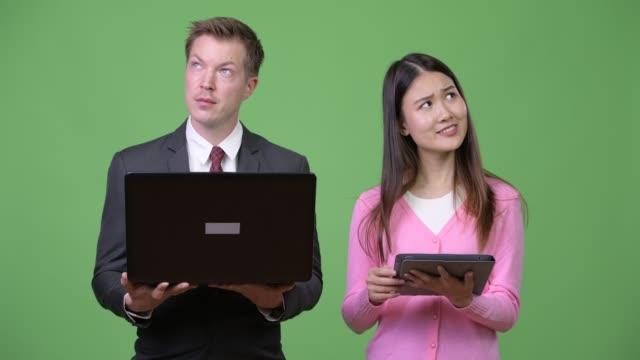 Junge-asiatische-Frau-und-junger-Geschäftsmann-mit-Laptop-und-digital-Tablette-zusammen
