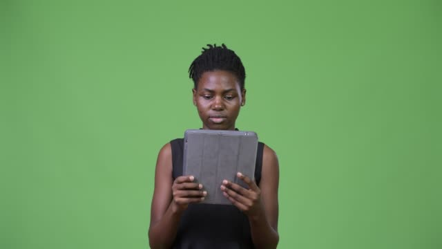 Young-beautiful-African-businesswoman-using-digital-tablet