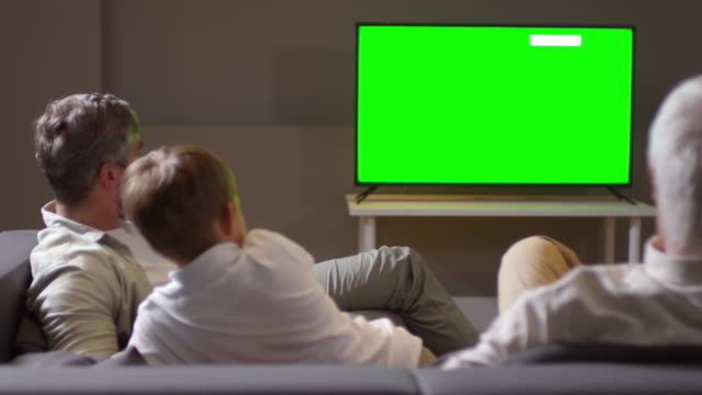 Dad-and-Son-Watching-TV-with-Family-and-Talking