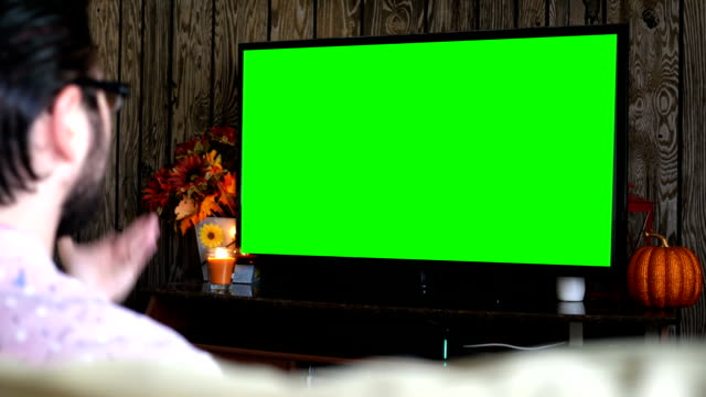 Angry-millennial-male-displeased-at-generic-sports-game-on-green-screen-TV