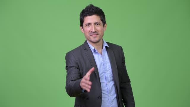 Happy-Hispanic-businessman-giving-handshake