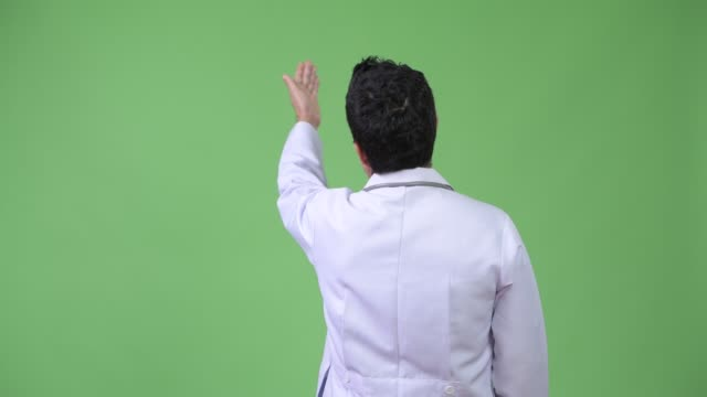 Rear-view-of-Hispanic-man-doctor-pointing-finger