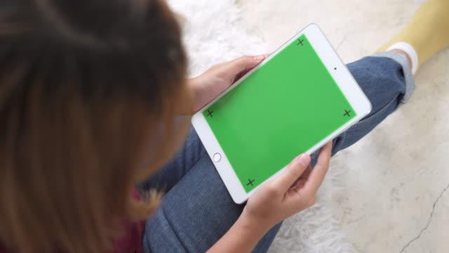 Joven-asiática-utilizando-dispositivo-tablet-negro-con-pantalla-verde-Mujer-asiática-con-tableta-desplazamiento-de-páginas-mientras-está-sentado-en-el-sofá-en-la-sala-de-estar-Clave-de-croma-
