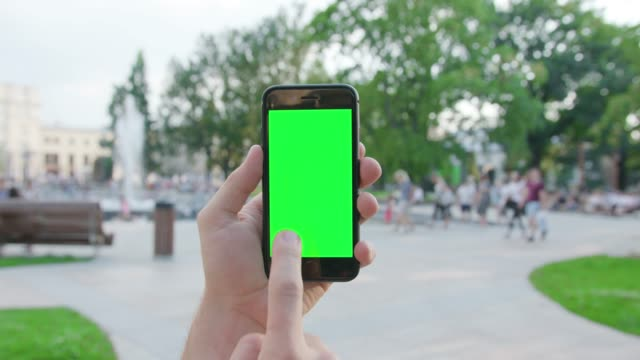 A-Hand-Holding-a-Phone-with-a-Green-Screen