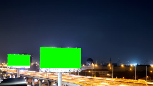 Green-screen-of-advertising-billboard-on-expressway-during-the-twilight-with-city-background-in-Bangkok-Thailand-