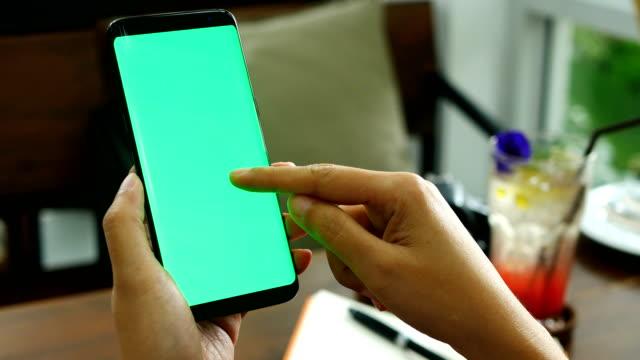 Imágenes-de-4K-cerca-mano-mujer-teléfono-inteligente-con-pantalla-verde-en-la-cafetería-con-toque-de-dedos-en-la-pantalla-teléfono