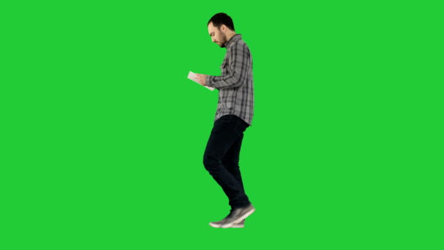 Confident-serious-man-walking-and-working-in-tablet-on-a-Green-Screen-Chroma-Key