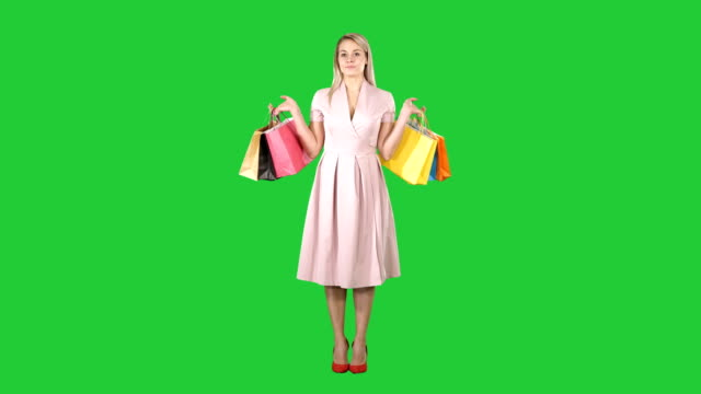 Woman-with-shopping-bags-in-pink-dress-standing-on-a-Green-Screen-Chroma-Key