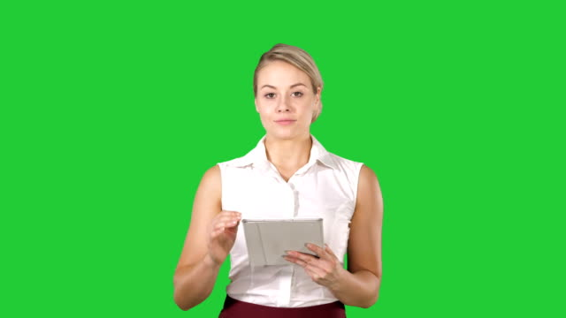 Beautiful-girl-holding-a-tablet-touch-pad-computer-gadget-swiping-pages-and-looking-in-camera-on-a-Green-Screen-Chroma-Key