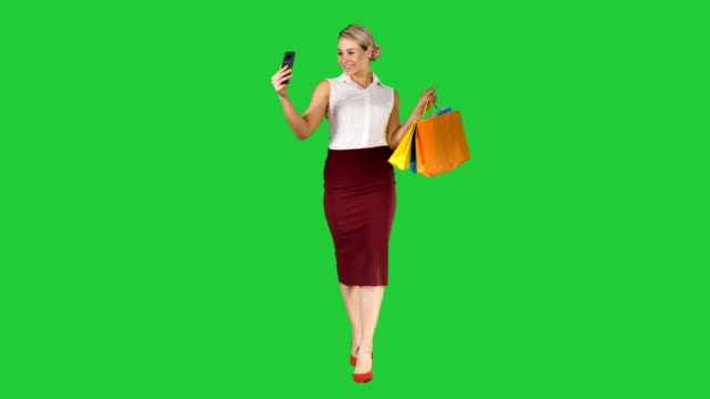 Ð¡heerful-woman-with-shopping-bags-taking-selfie-on-a-Green-Screen-Chroma-Key