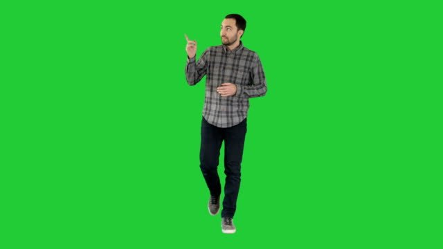 Young-confident-man-in-shirt-and-jeans-walking-towards-camera-and-pointing-to-the-sides-on-a-Green-Screen-Chroma-Key