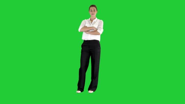 Atractivo-sonriente-mujer-de-negocios-de-pie-con-los-brazos-cruzados-y-mirando-a-cámara-en-una-pantalla-verde-Chroma-Key