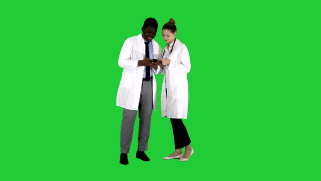 Medical-team-looking-at-phone-together-on-a-Green-Screen-Chroma-Key