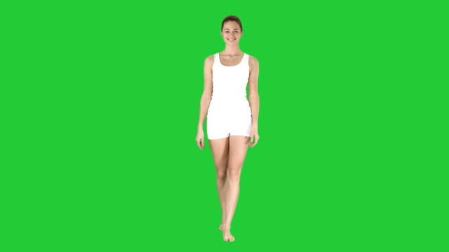 Young-sexy-woman-walking-and-smiling-dressed-in-white-shorts-and-t-shirt-on-a-Green-Screen-Chroma-Key