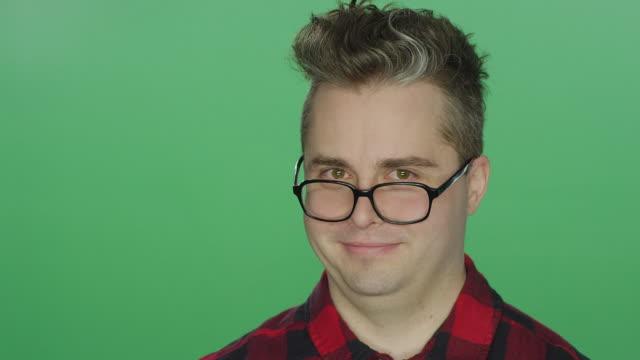 Hombre-joven-con-gafas-mirando-adelante-sobre-un-fondo-de-estudio-de-pantalla-verde