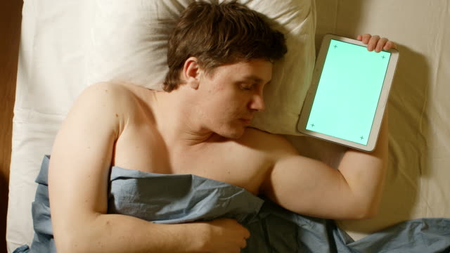 Caucasian-young-man-sleeps-and-holds-a-tablet-PC-in-hand-(green-screen)