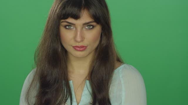 Beautiful-brunette-woman-seductively-staring-on-a-green-screen-studio-background
