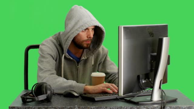 Tiro-medio-de-un-Hacker-con-Hoodie-sentado-en-su-computadora-de-escritorio-El-fondo-de-pantalla-verde-
