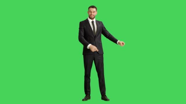 Long-Shot-of-a-Handsome-Smiling-Businessman-Making-Finger-Guns/-Presenting-Gesture-Background-is-Green-Screen-