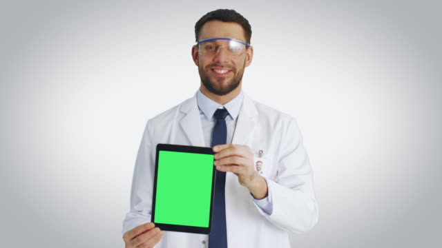 Mid-Shot-of-a-Smiling-Scientist-Presenting-To-Us-Tablet-Computer-with-Isolated-Mock-up-Green-Screen-Shot-with-White-Background-