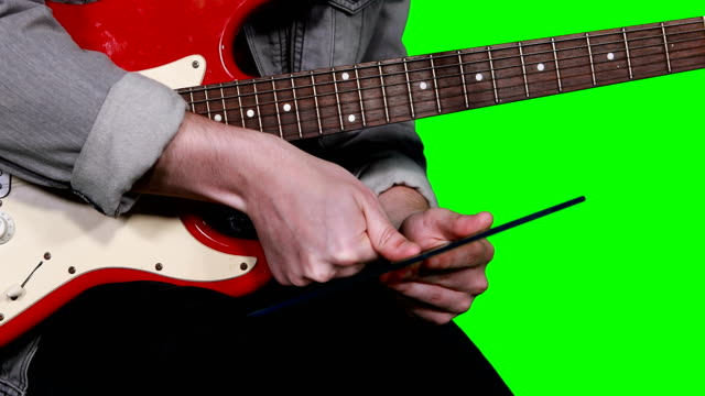 Man-holding-digital-tablet-while-playing-guitar
