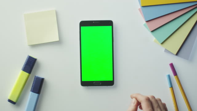 Designer-is-Using-Android-Phone-with-Green-Screen-in-Portrait-Mode-Top-View-