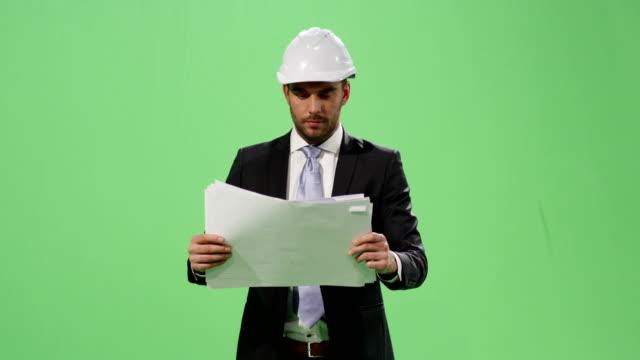 Empresario-en-un-casco-y-un-traje-es-caminar-y-buscar-en-documentos-en-papel-en-una-maqueta-pantalla-verde-de-fondo-