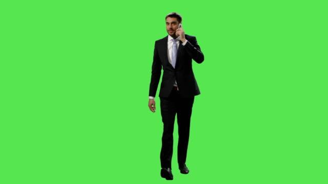 Empresario-en-un-traje-es-caminando-y-hablando-por-celular-en-una-maqueta-pantalla-verde-de-fondo-