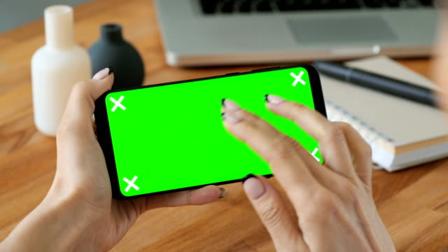 Person-using-cell-phone-with-green-screen-display-in-hand