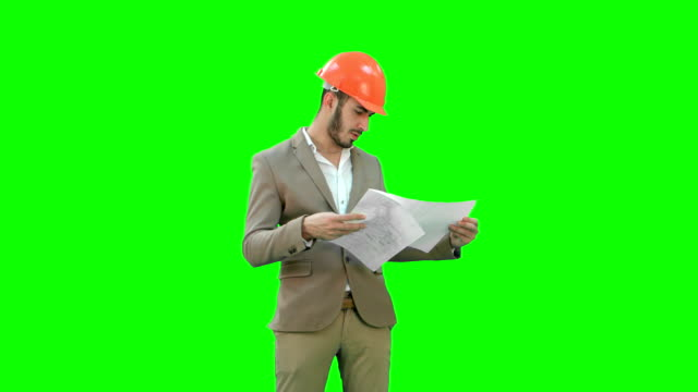 Architect-in-helmet-checking-construction-plan-on-a-Green-Screen-Chroma-Key