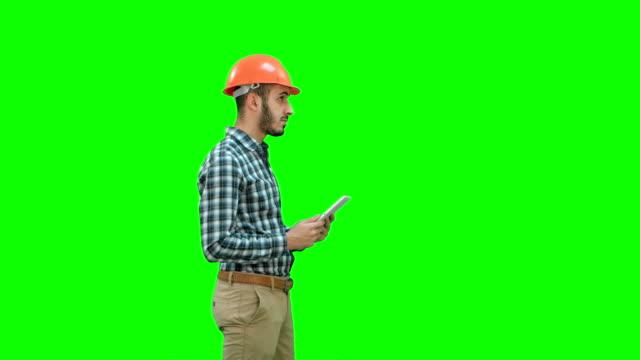 Ingeniero-contratista-en-casco-inspección-de-obra-con-tableta-digital-en-una-pantalla-verde-Chroma-Key