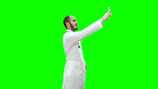 Sonriente-médico-de-bata-blanca-con-estetoscopio-tomando-selfie-en-su-teléfono-en-una-pantalla-verde-Chroma-Key