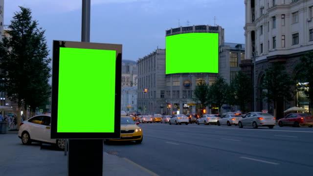 Dos-vallas-publicitarias-con-una-pantalla-verde-Por-la-tarde-en-una-calle-muy-transitada-