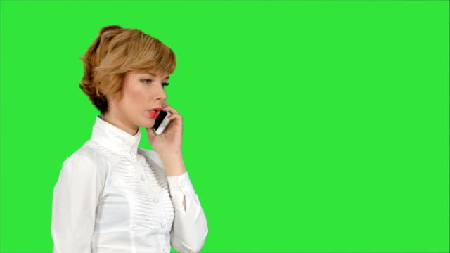 Happy-businesswoman-speaking-at-the-phone-on-a-Green-Screen-Chroma-Key