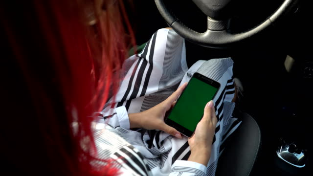 business-girl-in-smart-clothes-using-her-smartphone-in-her-car-direction-green-screen-chroma-key-4k