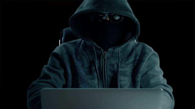 Man-in-hood-sitting-at-table-and-coding-on-laptop-Front-view-close-up-Hacker-in-balaclava-mask-and-glasses-working-at-computer-Surfing-internet-man-at-concrete-background-Alpha-channel-chroma-key-