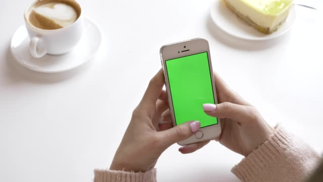 Beautiful-female-hands-using-a-smartphone-in-a-cafe-green-screen-concept-60-fps