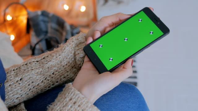Mujer-mirando-el-teléfono-inteligente-con-pantalla-verde