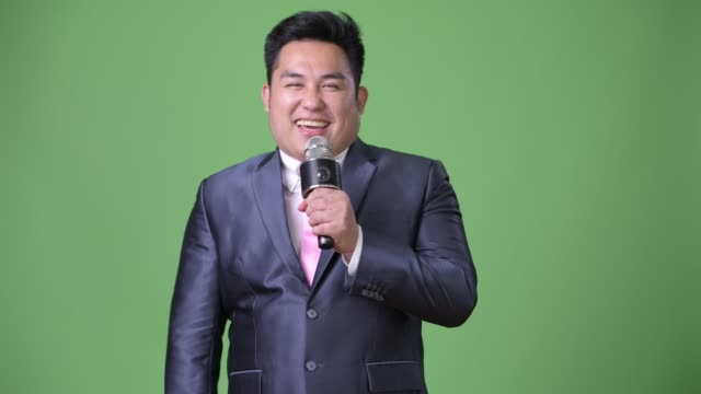 Young-handsome-overweight-Asian-businessman-against-green-background