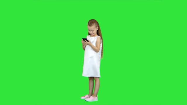 Linda-niña-sonriendo-y-utiliza-un-móvil-de-teléfono-en-una-pantalla-verde-Chroma-Key