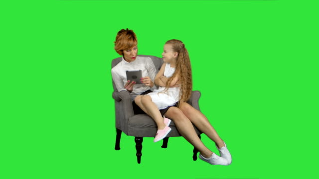 Caucasian-mum-and-daughter-use-tablet-on-a-Green-Screen-Chroma-Key