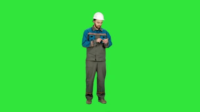 Bauarbeiter-mit-Handy-senden-SMS-auf-einem-grünen-Bildschirm-Chrominanz-Schlüssel