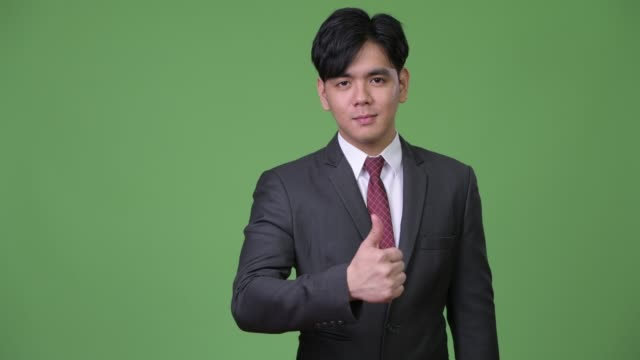 Young-handsome-Asian-businessman-giving-thumbs-up
