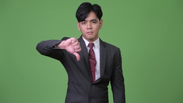 Young-handsome-Asian-businessman-giving-thumbs-down