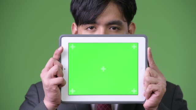 Young-handsome-Asian-businessman-using-digital-tablet