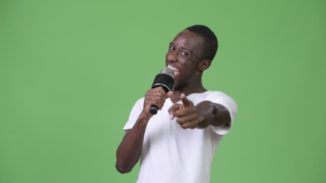Young-happy-African-man-smiling-while-speaking-on-microphone