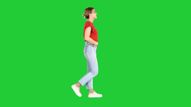 Fit-girl-holding-her-hands-in-the-pockets-of-blue-jeans-walking-on-a-Green-Screen-Chroma-Key