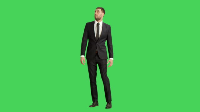 Long-Shot-of-a-Handsome-Businessman-Looking-Around-Frightened-Shot-on-a-Green-Screen-Background-